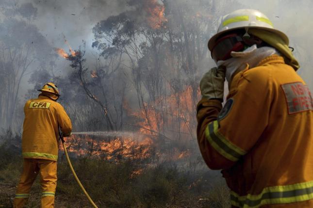 Dos bomberos trabajan hoy en las labores de extinción de un incendio forestal en la zona de Blue Mountains al oeste de Sídney